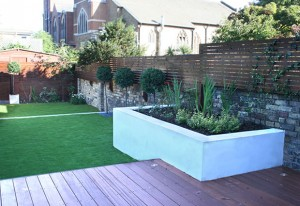 Family garden in Wandworth SW18, large artificial lawn, hardwood terrace decking, storage unit, rendered raised bed