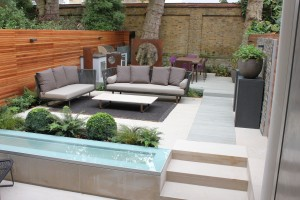 Garden Design in Chelsea SW3 - seating area, bespoke Corten-Steel panel, rustic slate feature wall, bespoke pedestals, designed furnitures, bespoke barbecue unit, planting design chelsea, ferns, box balls